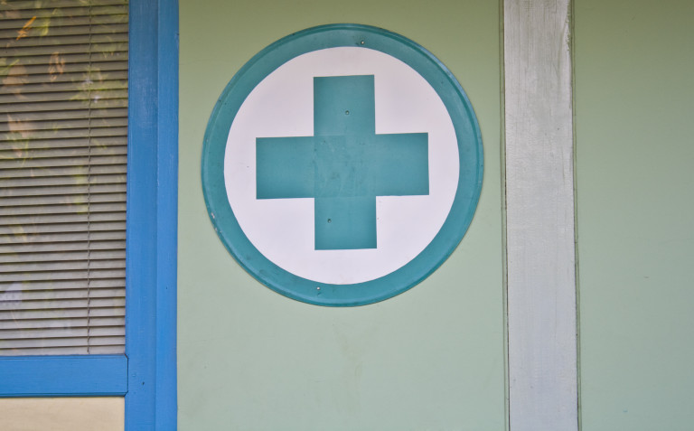 Healthcare house with health cross symbol in front of home.